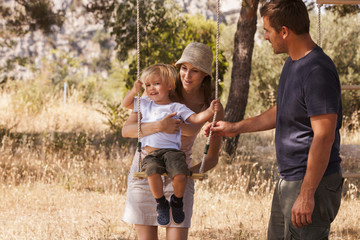 Croatia, Dalmatia, Parents playing with child on swing