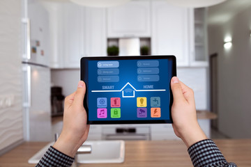 male hands holding tablet with app smart home kitchen house