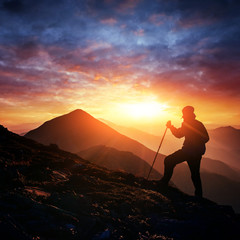 Happy man standing on a cliff at sunset
