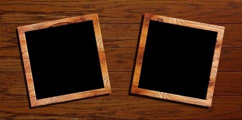 zwei kleine Bilderrahmen vor einem Holzhintergrund