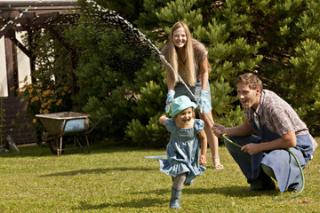 Parents and daughter playing together in the garden, Munich, Bavaria, Germany