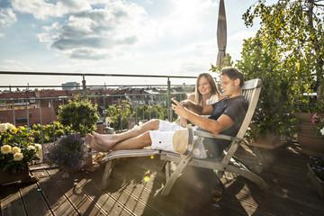Couple On Balcony Using Mobile Phone, Munich, Bavaria, Germany, Europe