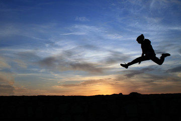 Child jumping over rocks