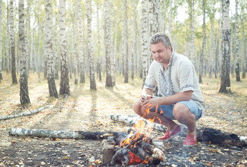 Picnic in a birch grove. Man sits near the bonfire with paper cup in hands.