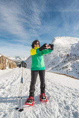 Active healthy smiling woman taking selfie.with her phone camera and sharing with friends or family. Self picture of Fit female enjoying snow season vacations on the top of a snowy mountain.