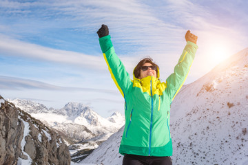 Active healthy smiling woman rising arms in success sign reaching the top of a snowy mountain. Fit female enjoying snow season vacations outdoor on a sunny happy leisure day.