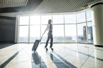 Woman with lagguge in international airport walking in terminal