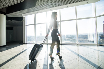 Business woman with luggage in international airport terminal waiting flight.