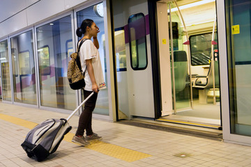 woman with luggage entering the train