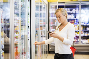 Woman Holding Mobile Phone At Grocery Store