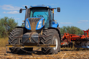 Big tractor plows the field and removes the remains of previously mown sunflower. Work agricultural machines.