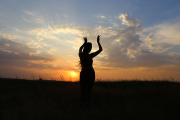 Slim girl showing various poses and dancing in a field outdoors