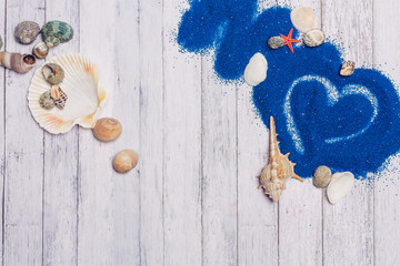 blue sand, seashells on a wooden background