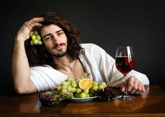 half naked curly guy at the table with a plate of grapes and a glass of wine photo