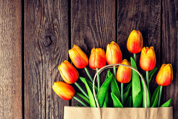 Bouquet of tulips in a paper shopping bag on a wooden background, concept of discounts and sales on the Women's Day or Mother's Day or Easter