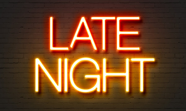 Late night neon sign on brick wall background.