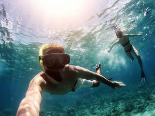 Making selfie underwater. Couple snorkeling in deep blue sea.