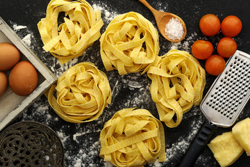 Fettuccine pasta italian food still life rustic over black wood background.