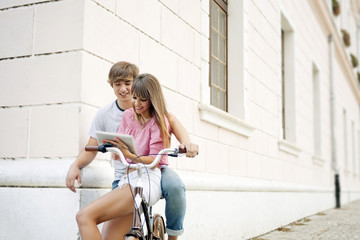 Young couple with bicycle, using digital tablet, Osijek, Croatia