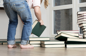 Little girl sits on the floor and play. Portrait of child has pile of books.