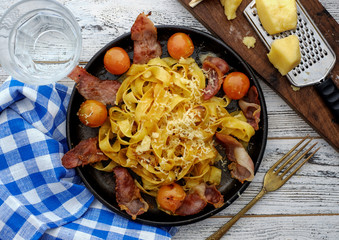 fettuccine pasta with cherry tomatoes and bacon.