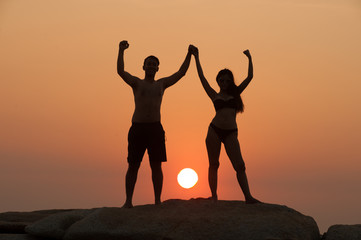 Positive couple holding hand up and expressing gladness while standing on stone in Sunset.