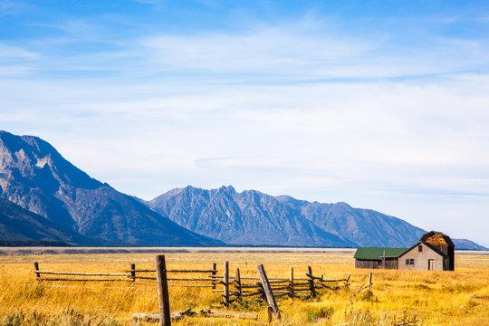 House and a Barn on a Golden Grass Prairie against the Grand Teton Mountains.  Near Moulton Barns.  Grand Teton National Park, Jackson Hole, Wyoming, USA.