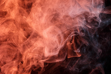 Abstract smoke Weipa. Personal vaporizers fragrant steam. The concept of alternative non-nicotine smoking. Orange smoke on a black background. E-cigarette. Evaporator. Taking Close-up. Vaping.
