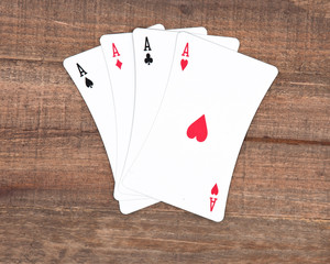 Four poker playing cards on vintage wooden background