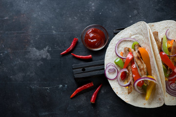 Wheat wraps with fajitas on a scratched metal surface, copyspace