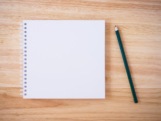 white cover notebook top view with pencil on brown wood desk
