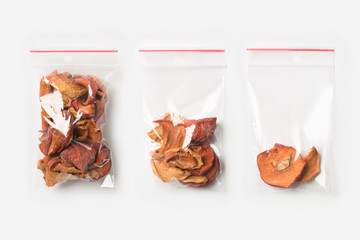 Set of three EMPTY, HALF AND FULL Plastic transparent zipper bag with home dried apples isolated on white. Vacuum package mockup with red clip. Concept.