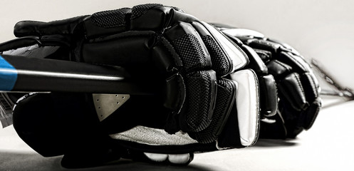 Hockey gloves and stick on white background