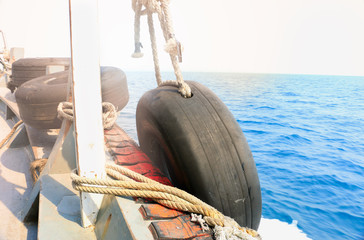 Rubber wheel on the transportation boat for moor, Tire tied to a boat moored at the dock