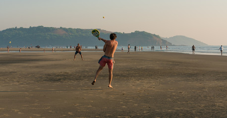 men play with a ball and rackets on the beach
