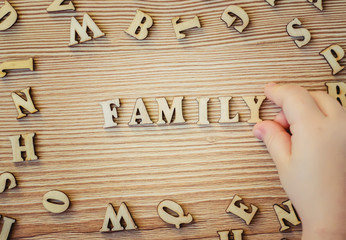 the child collects the important words from wooden letters. selective focus.