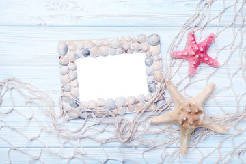 Frame of sea shells with starfish on wooden table