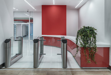 The turnstiles and a pass office at the entrance. Red and white design interior.