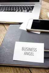 Business Angel on business card with electronic devices on office table