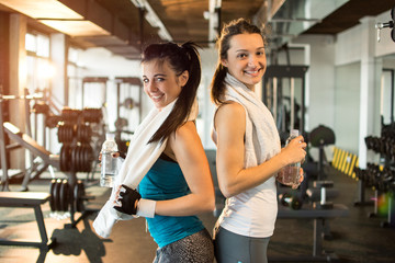 Two young sporty women in the gym.