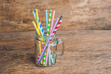 Vintage mason jar and multicolored spiral straws. wedding decor concept. Sweet table. A table with a drink concept.