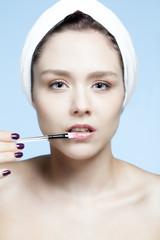 Portrait d'une jeune femme se faisant maquiller les lèvres