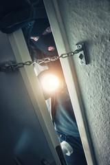 Einbrecher öffnet Tür mit taschenlampe