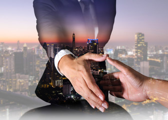 Businessman will handshaking for business relationship, city, cityscape and urban at night as Commitment and Partnership concept.