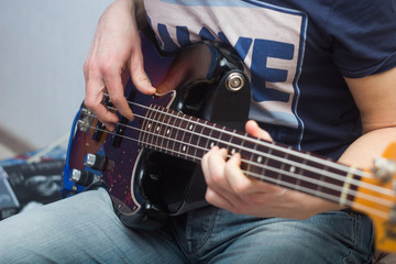 young man plays bass guitar