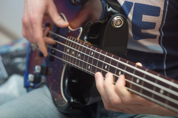 young man plays bass guitar