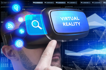 Business, Technology, Internet and network concept. Young businessman working in virtual reality glasses sees the inscription: Virtual reality