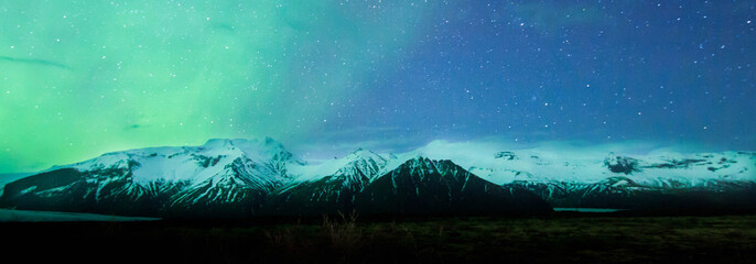 Aurora borealis display, northern lights in Iceland with mountain view in Skaftafell National Park