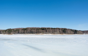 Peaceful frozen lake with blue sky