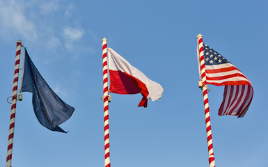 Flags of Nato, Poland and USA outdoor against clear blue sky.